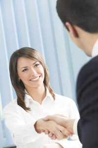 Two businesspeople, or business person and client handshaking at